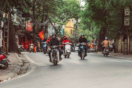 HANOI, VIETNAM - DECEMBER 15, 2018 : Street scene of the Old Quarter of Hanoi during the day. Lots of people and traffic in the narrow street.