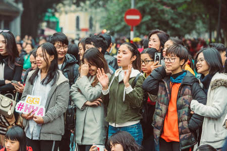 HANOI, VIETNAM - DECEMBER 15, 2018 : Street scene of the Old Quarter of Hanoi during the day. Lots of young people in the watching street show. Editöryel
