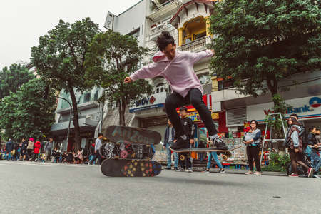 HANOI, VIETNAM - DECEMBER 14, 2018 : Street scene of the Old Quarter of Hanoi during the day. Young people skateboarding in the street. Editöryel