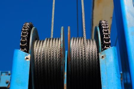 poleas: Poleas de cable de acero contra el cielo azul claro.