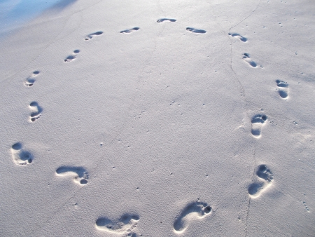 Footprints in circle on wet beach sand