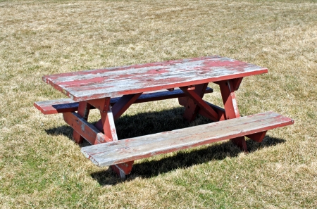 Empty weathered picnic table on dry grass  photo