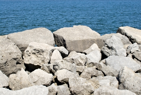 White boulders and rocks against rippled blue water  photo