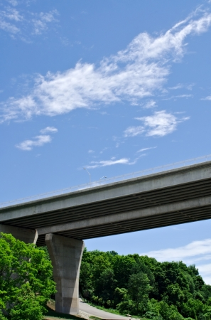 underneath: Pair of large concrete highway bridges crossing forest against partly cloudy sky  Stock Photo