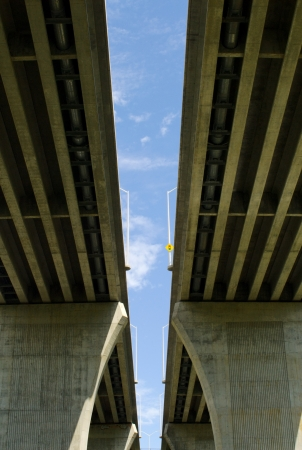 Between underside of pair of large concrete highway bridges against partly cloudy blue sky  photo