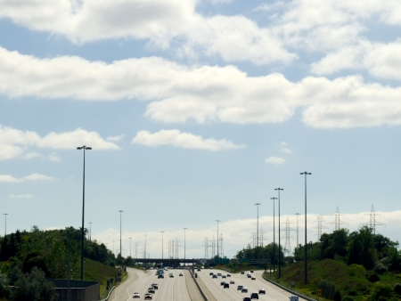expansive: Wide multi-lane highway against expansive partly cloudy sky between trees and lamp posts  Stock Photo