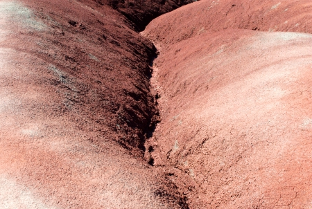 Eroded water channel between red clay badlands dunes  photo