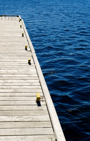 berth: Part of grey wooden dock with metal cleats on blue water