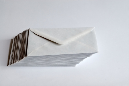 Stack of white envelopes shifted to right on white background