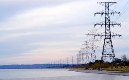 electric current: Row of large electrical towers receding into distance by shore
