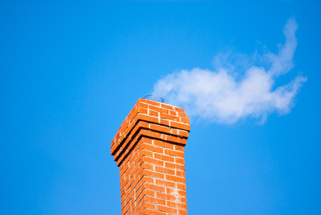 Red brick chimney releasing white smoke on clear blue sky