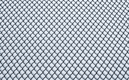 Black small chain-link fence covered in ice on white background
