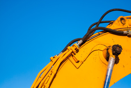 Part of yellow industrial machinery and hydraulics on clear blue sky  Archivio Fotografico