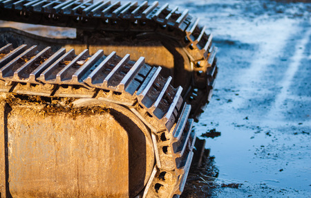 muddy tracks: Part of industrial caterpillar tracks in afternoon sun on muddy ground