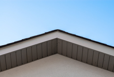 Top of residential house roof edge and siding against clear sky  Stock fotó
