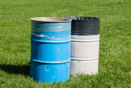Two large blue and grey garbage bins on green grass with garbage bags inside  photo