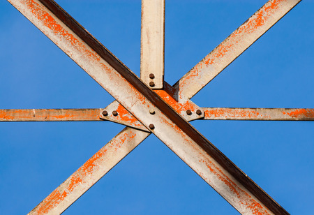 girders: Worn metal girders crossing held together with plates and screws