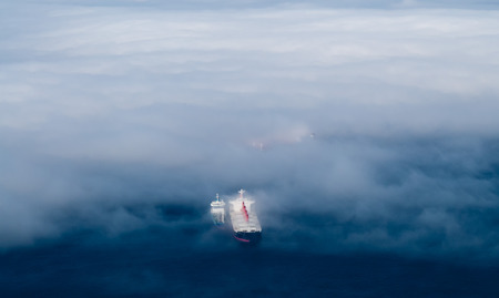Cargo ships emerging from thick fog  스톡 콘텐츠