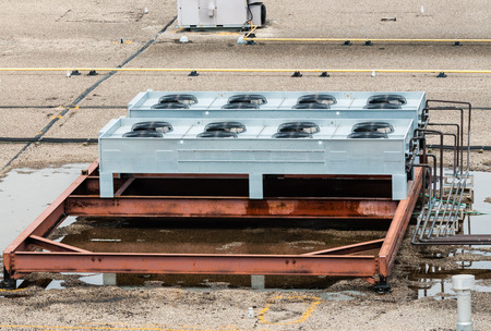 Ventilation fans and machinery on flat roof top.