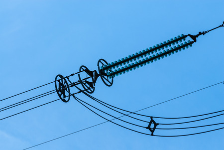 Close-up of insulator on high-voltage power lines against clear blue sky. Stockfoto