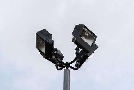 metal post: Set of four black flood lights at top of metal post on white sky.