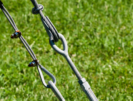 braided flexible: Pair of tight metal cables and loops holding each other against grass.