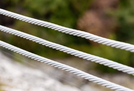 Close-up of three parallel metal cables on blurred background. Banco de Imagens