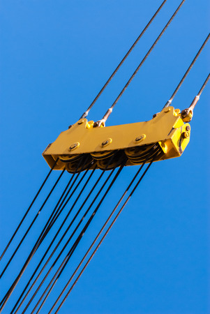 pulleys: Large yellow pulley assembly with three sets of pulleys and tightly stretched diagonal steel cables above and below. Stock Photo
