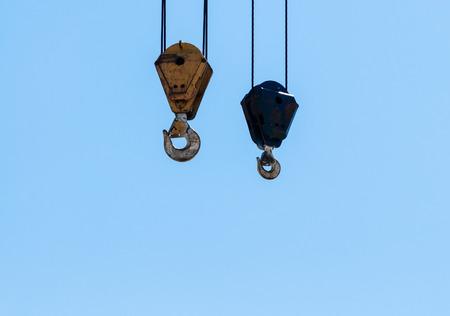 poleas: Dos ganchos de izado de gr�a sucios industriales y poleas que cuelgan por cables de acero en el cielo azul p�lido.