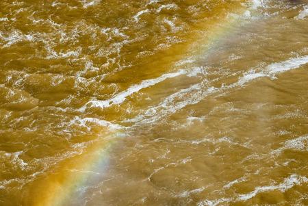 churning: Vivid rainbow diagonally across churning muddy brown river water waves and breakers.