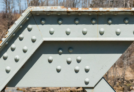 durable: Angled metal girder with rivets on painted steel surface and some rust partly casting shadows from top against blurred trees.