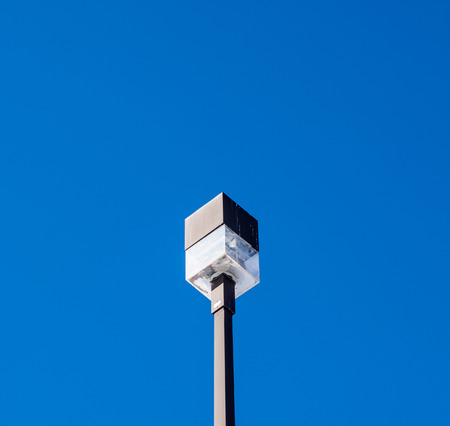 Cubeshaped street lamp from below on rectangular post against clear blue sky. Stock fotó