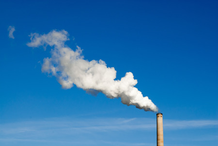 polluting: Industrial smokestack spewing white polluting smoke cloud horizontally from right to left into clear blue sky. Stock Photo