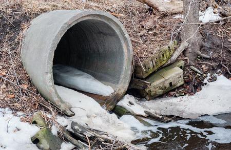 desague: Gran tubo de desagüe de alcantarillado de cemento de desembocar en charco espumoso de escombros en invierno rodeado de ramas de la suciedad y manchas de nieve.