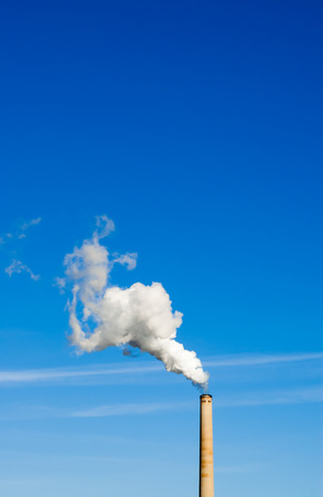 spewing: Industrial smokestack spewing white polluting smoke cloud vertically up and left into clear blue sky.