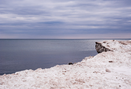 edge of the ice: Edge of dirty white ice and snow at coastline against purple overcast clouds and water horizon.