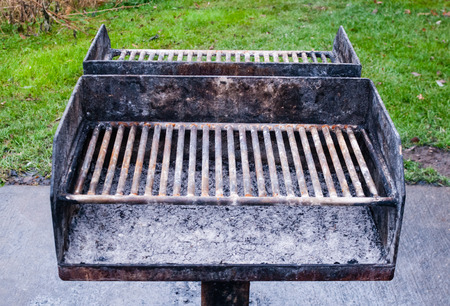 Dirty old metal barbecue grills on cement base and against grass with remains of gray ashes. Stock Photo