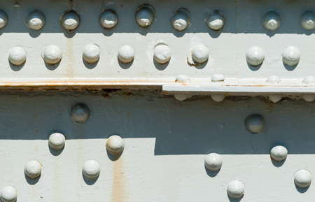 Closeup of rivets on painted steel surface with some rust stains partly casting shadows from top.