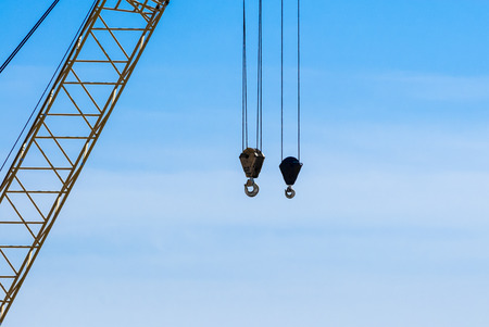 hoist: Two dirty industrial crane hoist hooks and pulleys hanging by steel cables with crane truss on left against blue and white sky. Stock Photo