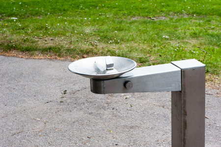 park path: Empty silver metal water drinking fountain near park path and grass.