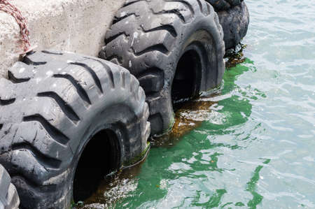 cushioning: Large old black tires being used as bumpers at concrete dock, partially submerged in green water.