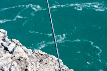 over the edge: Tight steel line extending over edge of rocky cliff and green river water below.