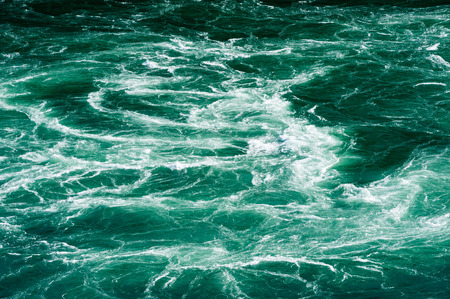 currents: Abstract powerful white water currents churning in flowing green river.