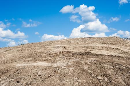 suelo arenoso: Montículo de tierra de arena con huellas de neumáticos y la oruga, que termina en el cielo azul con nubes cúmulos. Foto de archivo