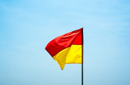 Red and yellow beach water safety flag against pale sky, fluttering in wind.