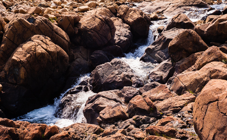 Stream of water flowing and splashing among bare red rocks,  at Tablelands, Gros Morne National Park, Newfoundland, Canada. Imagens