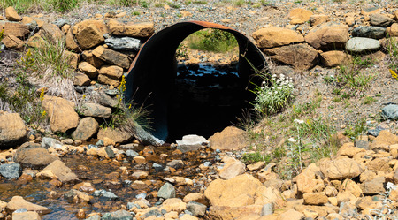 culvert: Looking through rusted corrugated culvert pipe embedded in rocky ground with water flowing from small stream.