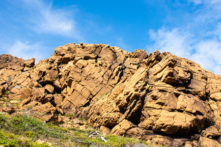 large formation: Large irregular cracked rock formation against partly cloudy blue sky, with green shrubs at base, at Tablelands, Gros Morne National Park, Newfoundland, Canada.