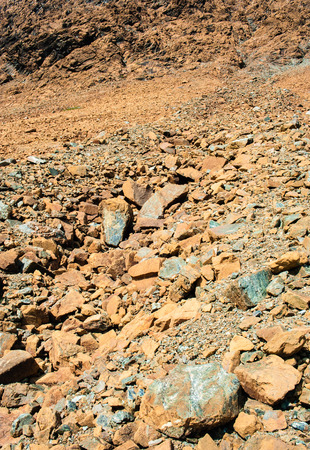 morne: Dry yellow jagged broken rock and stone debris from landslide on mountain slope, at Tablelands, Gros Morne National Park, Newfoundland, Canada.