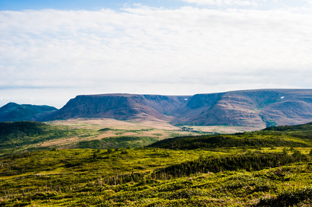 Green hills covered in vegetation leading to dry mountain plateau in distance, under cloudy sky, near Tablelands, Gros Morne National Park, Newfoundland, Canada.